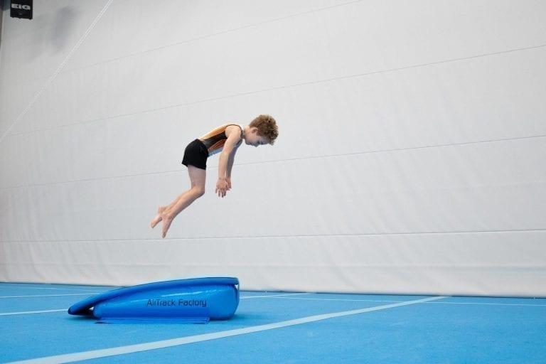 boy-gymnast jumping spring board airboard boost
