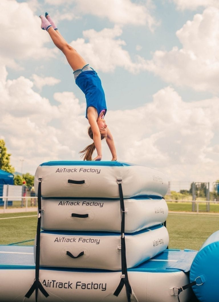 Gymnast with blue shirt performing a handstand outside