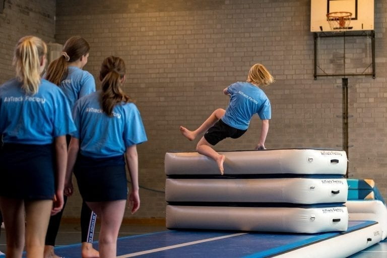 Girl jumping over Aand inflatable vaulting table in school
