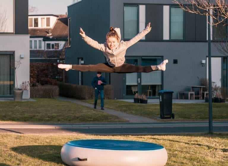 Girl jumping high on airspot outside