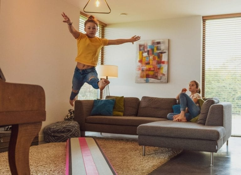 Girl leaping on pink AirBeam in livingroom