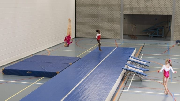 gymnasts tumbling on blue airtrack p3
