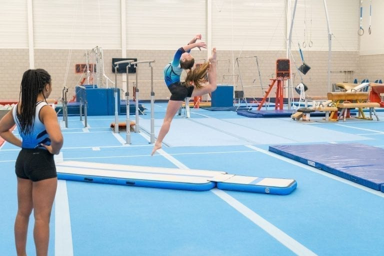 Gymnast leaping on blue inflatable AirFloor and AirBoard
