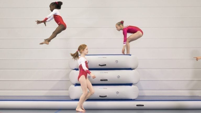 Gymnasts jumping over inflatable vaulting box
