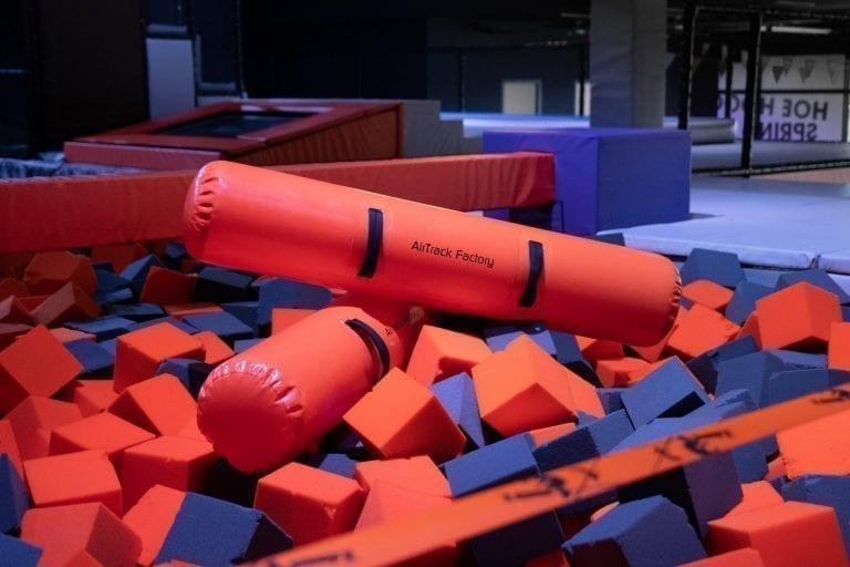 Orange inflatable BattleBeams in foam pit