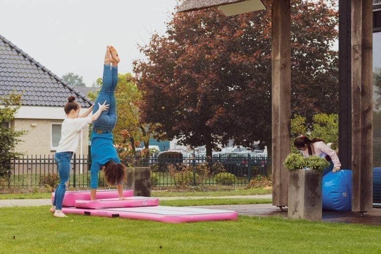 2 girls practicing gymnastics on pink inflatable training set in garden