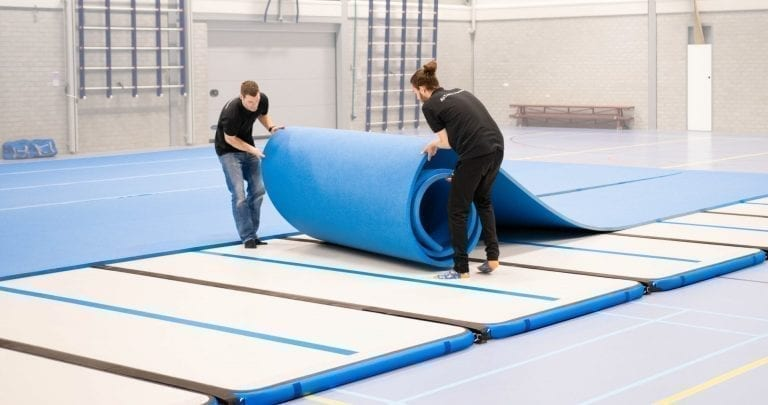 2 coaches setting up the inflatable competition floor