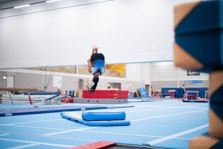 Girl gymnast jumping high on inflatable training set 2
