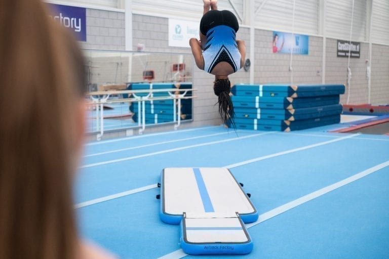 Girl gymnast jumping high on inflatable training set